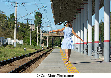 Young beautiful girl goes on the platform holding her arms outstretched to the side