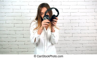 young beautiful girl having fun with headphones on white wall