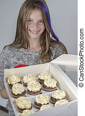 Young beautiful girl holds box of delicious cupcakes, closeup portrait indoors