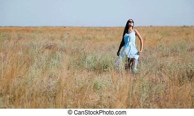 Young beautiful girl in a blue dress enjoys flowers steppe. A young woman in a meadow. Steppe. Blossoming sunny meadow with tall grass thick ears and flowers