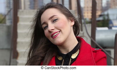 Young beautiful girl in a red coat smiling