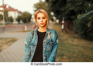 Young beautiful girl in a trendy denim jacket walking outdoors on a summer day