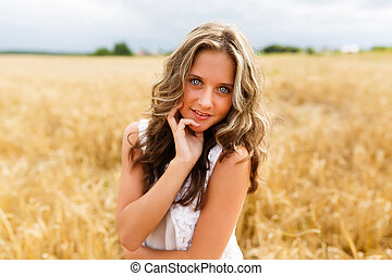 Young beautiful girl in a wheat field