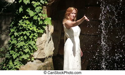 girl in a white dress is touching the water. It stands at the waterfall.