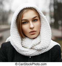 Young beautiful girl in a white knitted scarf in autumn day