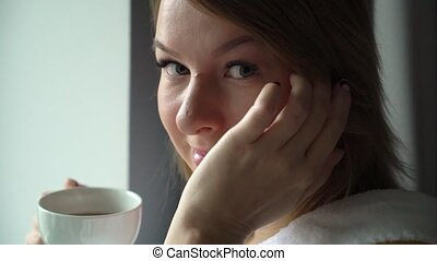 Young beautiful girl in bathrobe drinking coffee at the morning