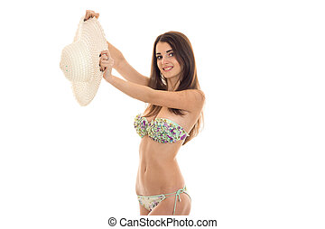 beautiful girl in bikini smiling and holding a hat isolated on white background