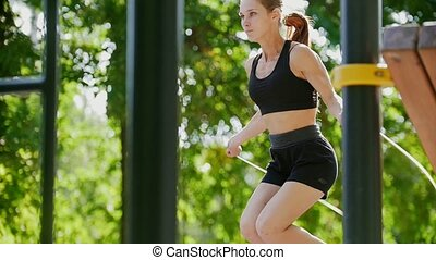 Young beautiful girl in black tracksuit jumping rope in the...