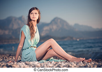Young beautiful girl in dress walks by the sea.