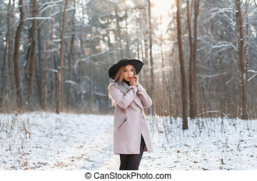 Young beautiful girl in fashionable clothes on a sunny winter day