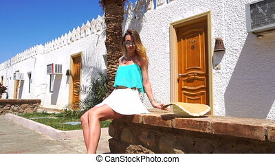 young beautiful girl in glasses sits on a stone on the street near the hotel's rooms in slow motion