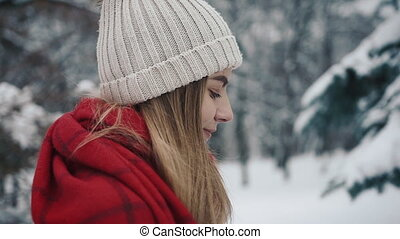 Young beautiful girl in in warm clothes standing near the Christmas Trees and and uses a smartphone. Slow motion. Portrait of stylish young beautiful girl in a winter park