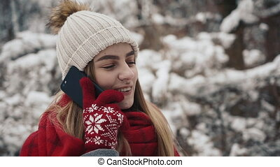 Young beautiful girl in in warm clothes standing near the Christmas Trees and speaks by phone. Slow motion. Portrait of stylish young beautiful girl in a winter park
