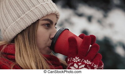 Young beautiful girl in in warm clothes standing near the Christmas Trees in snow drinking hot beverage from the paper cup. Slow motion. Close-up