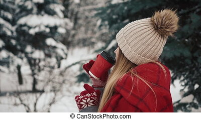 Young beautiful girl in in warm clothes standinh near the Christmas Trees in snow drinking hot beverage from the paper cup. Slow motion. Portrait of stylish young beautiful girl in a winter park