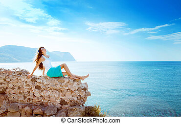 young beautiful girl in mountains on a background of the sea
