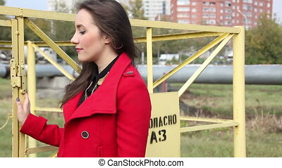 Young beautiful girl in red coat standing near the fence of the pipeline