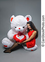 Young beautiful girl in red dress with big teddy bear soft toy happy smiling and playing on grey background