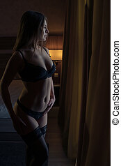 Young beautiful girl in sexy lingerie posing by the window