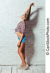 Young beautiful girl in shirt and shorts on a background of a br