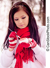 Young beautiful girl in snow forest painting heart. - Young...