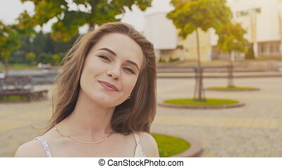 Young beautiful girl in summer dress in city park posing in front of camera, smiling and adjusting her long hair. Summer. Recreation. Youth.