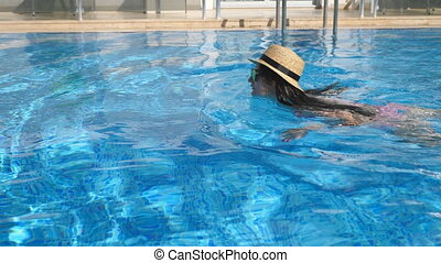 Young beautiful girl in sunglasses and hat swimming in pool....