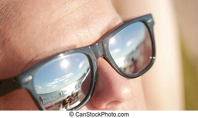 young beautiful girl in sunglasses. beach reflection. concept of holiday at sea