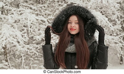 Young beautiful girl in the background of snow-covered fir trees in warm winter clothes with a hood is sheltered from frost. Enjoying the winter and falling snow.