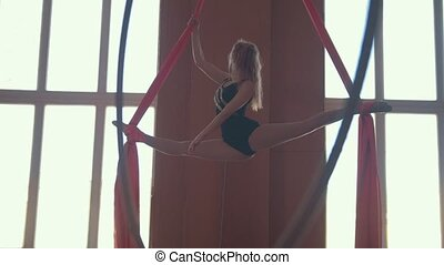 Young beautiful girl in the splits hanging on the hoop,...