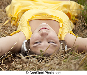 Young beautiful girl in yellow with headphones at field.