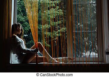 Young beautiful girl is sitting on the windowsill. Orange...