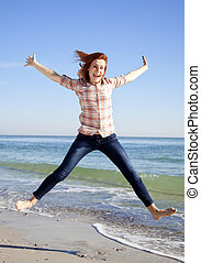 Young beautiful girl jumping at the beach.