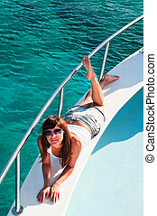 Young beautiful girl laying on a yacht with his legs hanging in the blue sea
