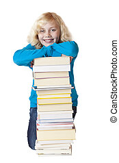Young beautiful girl leans on pile of books and smiles happily