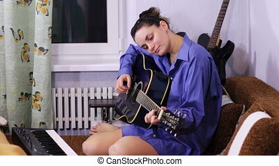Young beautiful girl learning to play the guitar at home.