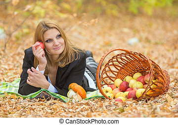 Young beautiful girl lies on the on the foliage in the autumn forest and dreaming holding an apple and looking to the right