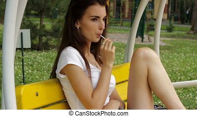 young beautiful girl looks forward and sucks a yummy...