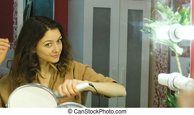 Young beautiful girl looks in the mirror and curls curls on the curling iron in the dressing room