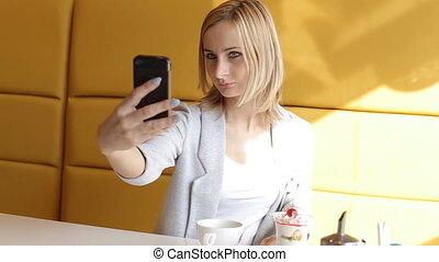 Young beautiful girl makes selfie in a cafe