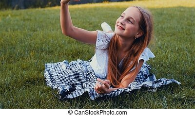 Young beautiful girl making selfie portrait using smartphone in green park, lying on the grass with mobile phone. Color graded