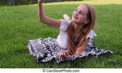 Young beautiful girl making selfie portrait using smartphone in green park, lying on the grass with mobile phone