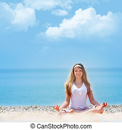young beautiful girl meditating on beach