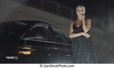 Young beautiful girl near a black car.