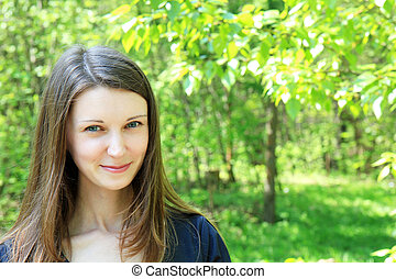 young beautiful girl on a background of green vegetation