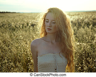 Young beautiful girl on a summer field
