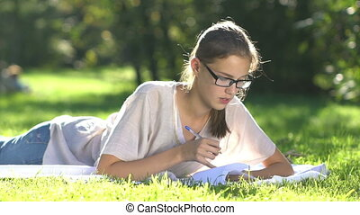 Young beautiful girl on meadow writes to notebook