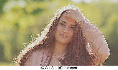 Young beautiful girl posing in front of the camera. A touch of the hand to long hair. Summer. Nature.