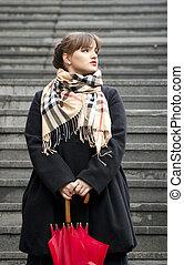 Young beautiful girl posing outdoors with umbrella