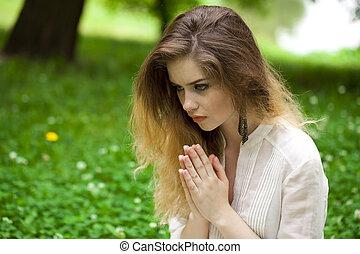 Young beautiful girl praying